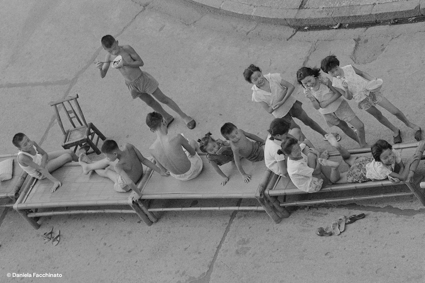 Xi'an, Shaanxi, China, 1976. Children eat their meals on cots along the pavements, after the Tangshan earthquake