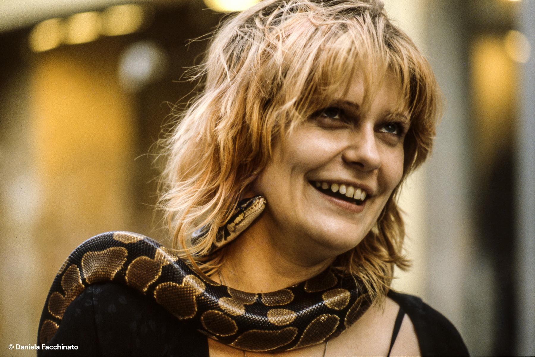 Punk girl walking along the Kurfürstendamm with a live snake around her neck. Berlin 1981