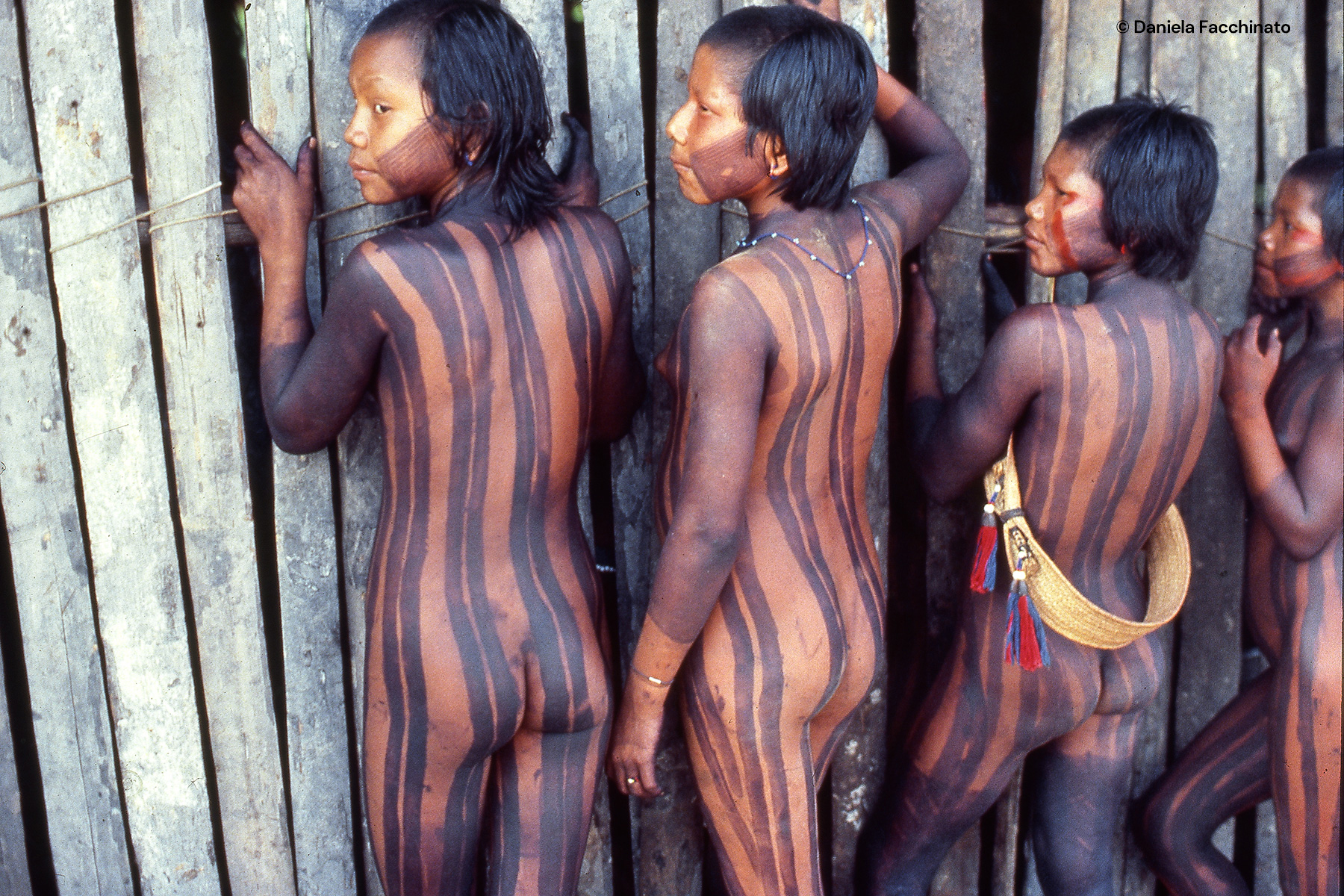Amazonia, Xingù. Young Kayapò indies spying inside the hut the meeting of the tribe chiefs