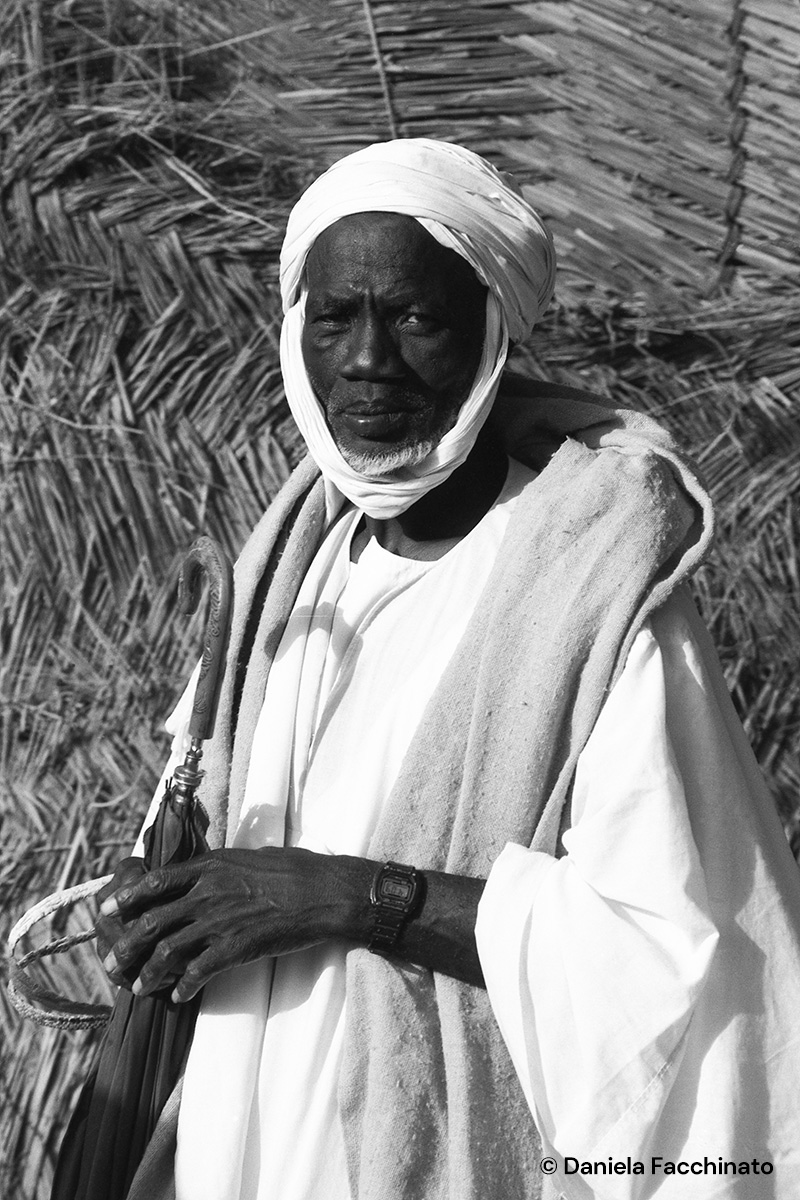 Djennè, Mali 1989. Welthy men use umbrellas to protect themselves from the sun